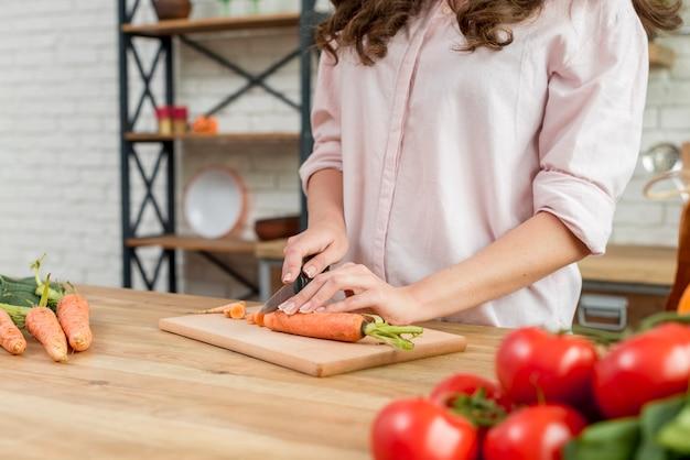 Brunette woman cutting carrots