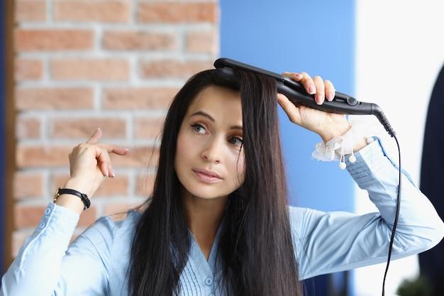 갈색 머리 여자는 컬링 아이언으로 그녀의 머리의 컬링