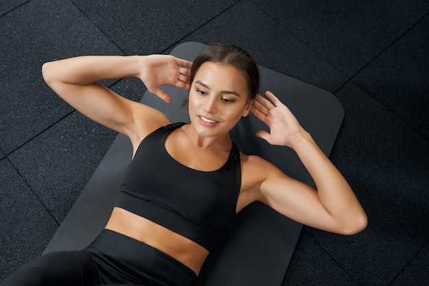Brunette woman doing abs on black mat in gym
