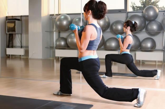 Brunette woman doing physical exercise lunges with dumbbells in hands near yoga mat at gym