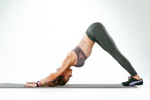 ジムでいくつかのストレッチ体操を行うブルネットの女性