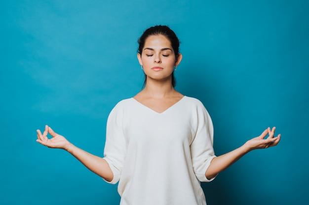 갈색 머리 여자는 눈을 유지하는 하얀 스웨터를 입고 실내 명상, mudra 제스처에 손가락을 유지하는 요가 연습하는 동안 폐쇄. 격리 된 파란색 배경입니다. 스튜디오 촬영