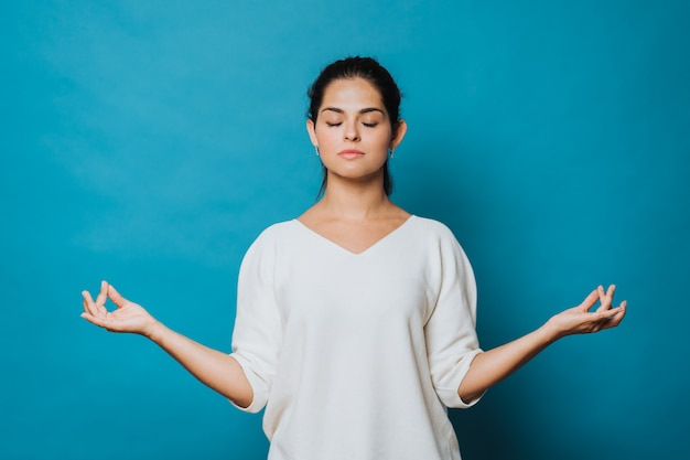 Brunette woman dressed in white sweater keeping eyes closed while meditating indoors, practicing yoga keeping fingers in mudra gesture. isolated blue background. studio shot