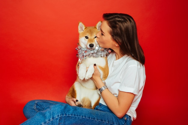 Brunette woman embracing and kissing shiba inu dog in silver decoration, red background.love to the animals