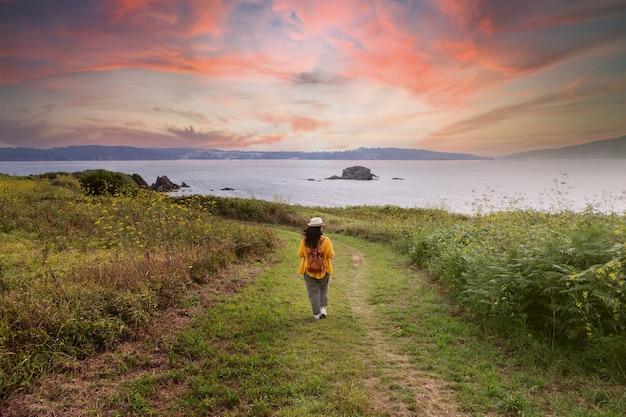 놀라운 하늘 아래 산책을 즐기는 갈색 머리 여자