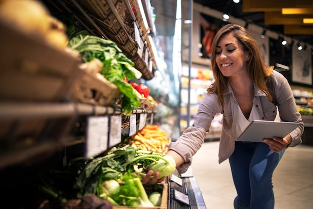 Brunette woman enjoys choosing food at supermarket