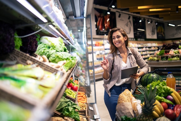 갈색 머리 여자는 슈퍼마켓에서 쇼핑 음식을 즐긴다