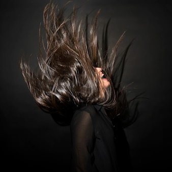 Brunette woman in evening wear with windy hairs
