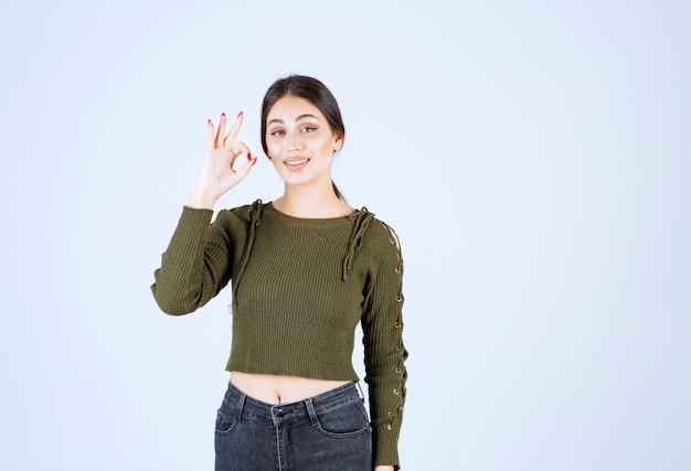 ブルネットの女性は、白い背景の上に立ったまま親指をあきらめます。