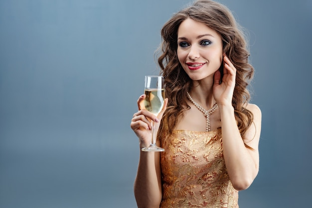 Brunette woman in golden dress and pearl necklace with raised glass of champagne and touch herself face for hand