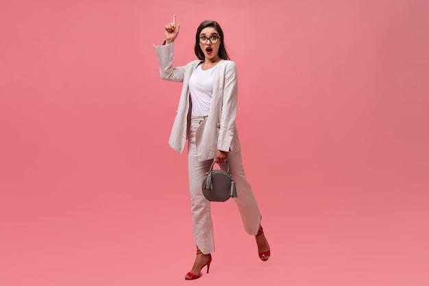 ブルネットの女性は素晴らしいアイデアとピンクの背景にポーズをとっています。スタイリッシュな服を着て、灰色のハンドバッグを持った美しいビジネスレディが動きます。