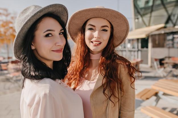 Donna castana in cappello allegramente guardando sopra la spalla mentre posa con un amico