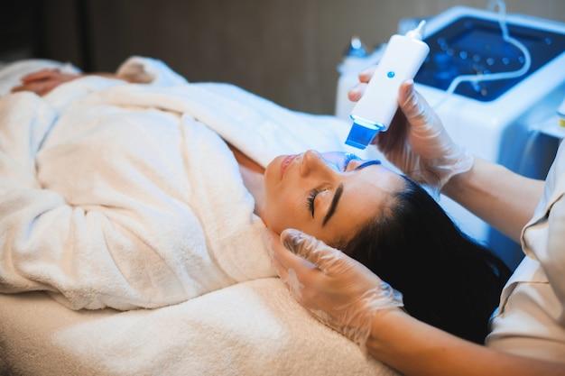 Брюнетка женщина, имеющая спа-процедуру в салоне, лежа на тренере и терпеливо ожидая