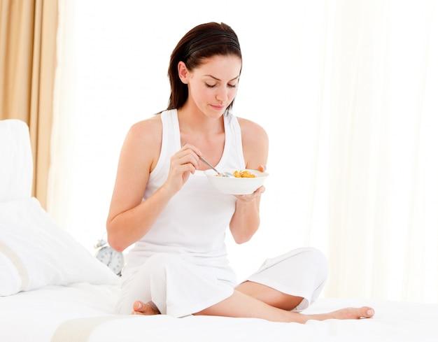 Brunette woman having breakfast sitting on her bed