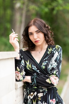 Brunette woman having a cigarette and looking at the camera