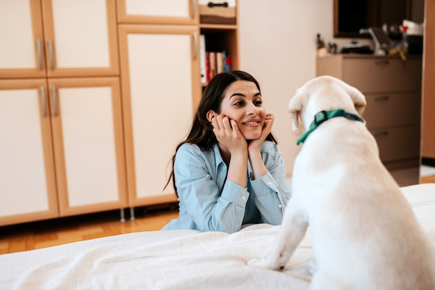 Brunette woman having fun with her dog in apartment.