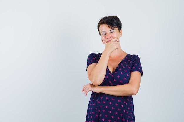 紫と赤の模様のドレスで歯痛があり、疲れ果てているように見えるブルネットの女性。正面図。