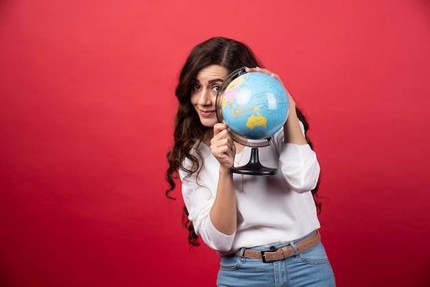 赤の背景に地球の後ろに隠れているブルネットの女性。高品質の写真