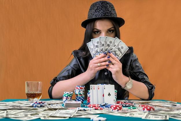 Брюнетка женщина, пряча лицо под вентилятором долларов