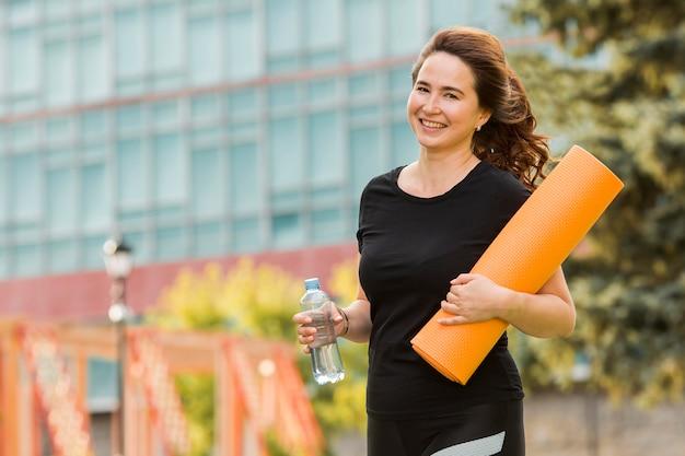 Брюнетка женщина, держащая коврик для йоги с копией пространства