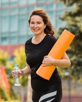 Брюнетка женщина, держащая коврик для йоги