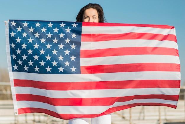 Брюнетка держит большой флаг сша над собой