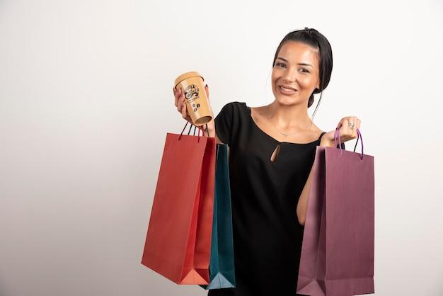 Donna castana che tiene mazzo di borse della spesa e tazza di caffè.