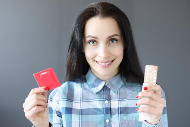 Брюнетка женщина, держащая презерватив и противозачаточные таблетки, выбирая противозачаточные средства от нежелательных