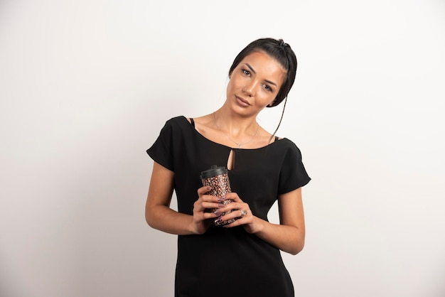 Brunette woman holding cup of coffee tightly.