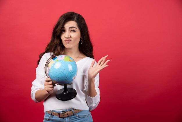 地球儀を持ち、顔を作るブルネットの女性。高品質の写真