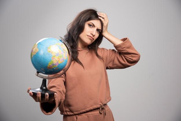 問題を抱えている地球を保持しているブルネットの女性