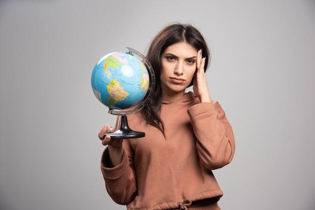 灰色の地球を保持しているブルネットの女性
