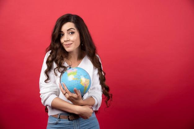 赤の背景に地球儀を持ったブルネットの女性。高品質の写真