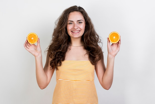 Brunette woman holding an orange