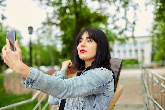 Брюнетка женщина, держащая бумажные хозяйственные сумки и делающая селфи смартфоном в парке
