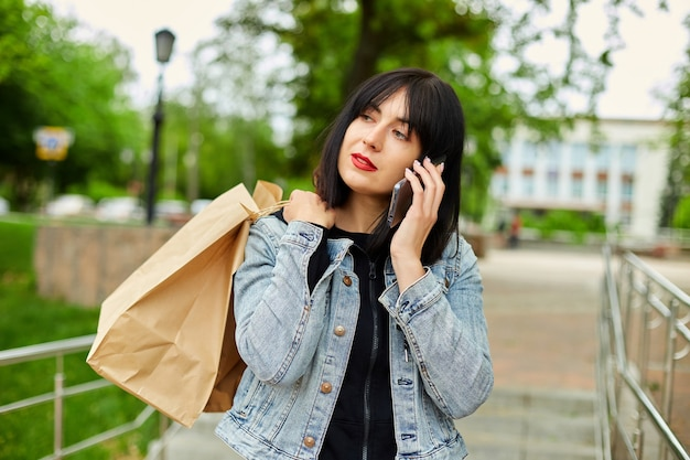 Брюнетка женщина держит бумажные хозяйственные сумки и разговаривает по телефону