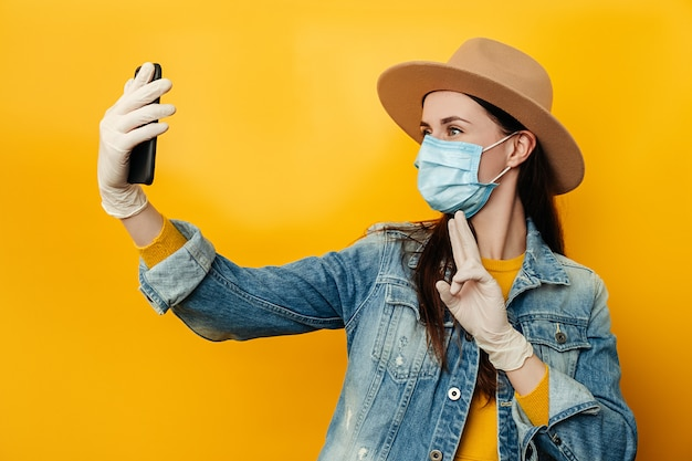 Brunette woman holding phones in hands makes selfie, against yellow background, dressed in denim jacket, wears protective medical mask to protect herself from coronavirus. social distancing concept