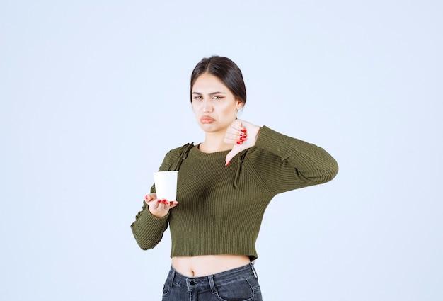 Donna castana che tiene tazza di plastica e dà i pollici in giù.