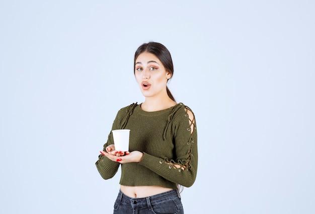 흰색 바탕에 플라스틱 컵을 들고 갈색 머리 여자.