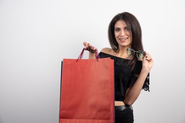 쇼핑백과 안경 들고 갈색 머리 여자