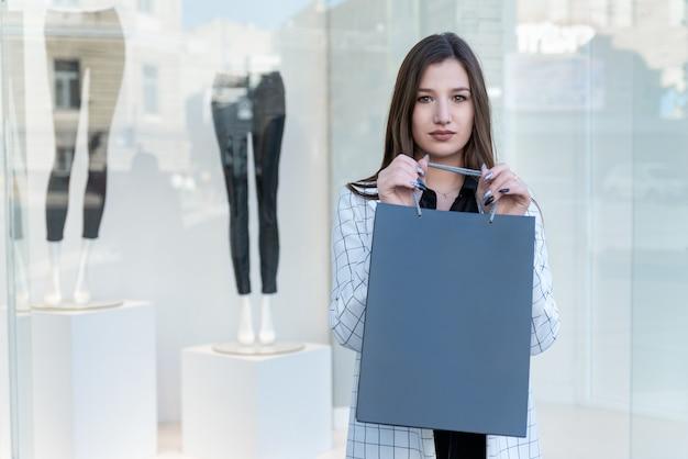 ブルネットの女性は、shopwindowの背景に買い物袋を保持します。モックアップ。ブラックフライデーの買い物、割引。