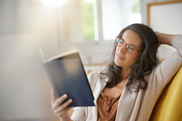 Brunette woman at home reading book