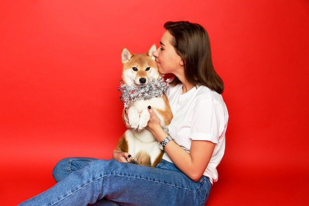 Brunette woman hugging, embracing shiba inu dog in christmas decorations, red background. love to the animals