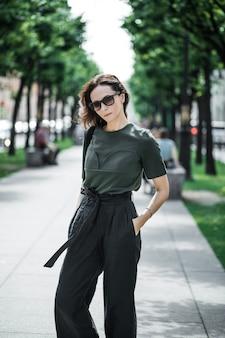 緑のトップと黒のズボン、サングラスのブルネットの女性。