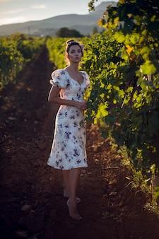 白いドレスを着たブルネットの女性は、イタリアの夏のブドウ園に立っています