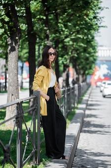 노란 재킷과 검은 바지, 선글라스와 가방 문자열 가방에 갈색 머리 여자.