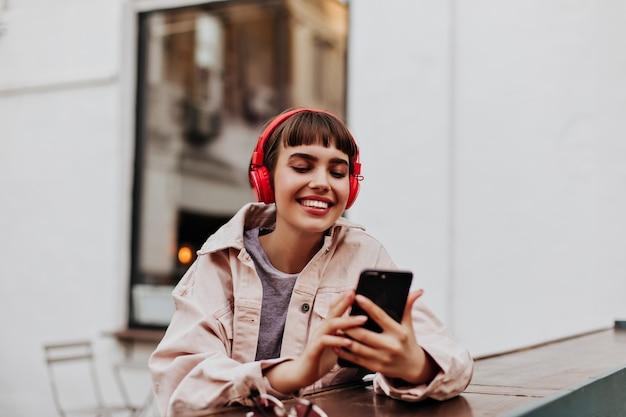 電話を保持し、外で音楽を聴いているベージュのジャケットのブルネットの女性