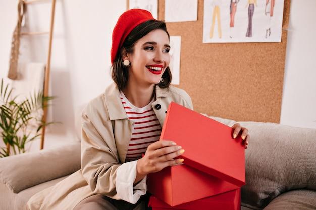 Брюнетка женщина в бежевом окопе улыбается и открывает красную коробку. красивая милая девушка в полосатом свитере и яркой шляпе улыбается.
