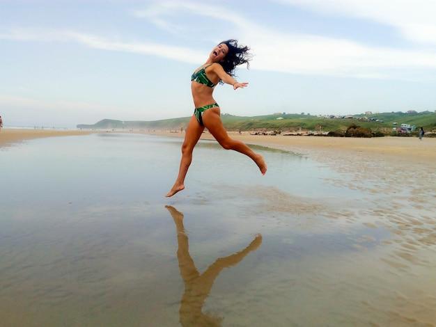 ビーチで喜びのためにジャンプする彼女の自由な時間を楽しんでいるビキニのブルネットの女性