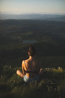 山の頂上に座って景色を楽しむブラジャーのブルネットの女性